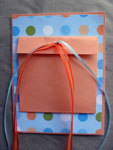 After enclosing the sendable item(s), pull all ends of the ribbon through the single hole in the flap...
