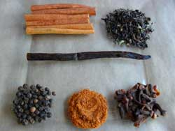 Wholes spices like cinnamon sticks, cloves, vanilla bean and peppercorns and Darjeeling black tea for chai tea mix