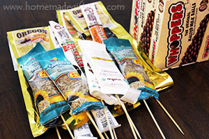 Attaching wholesome snacks like local beef jerky, nuts and health bars to wooden skewers, allows you to turn them into a fun and edible homemade gift arrangement.